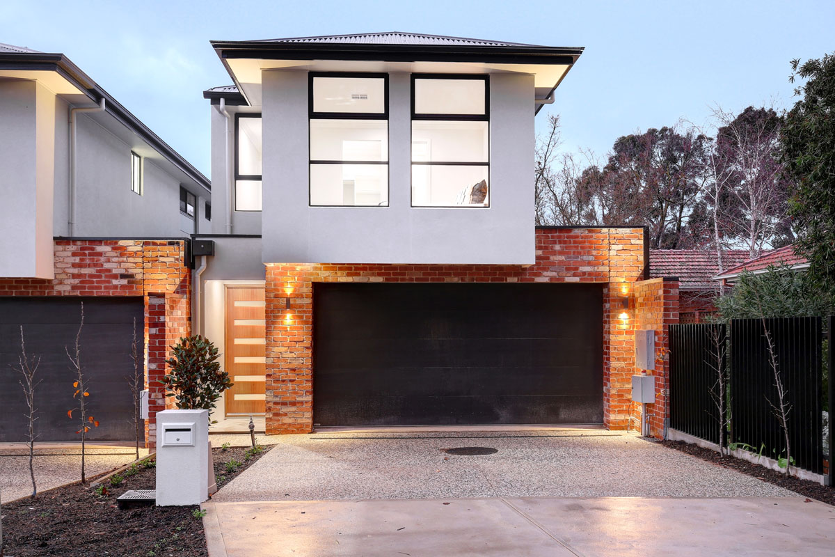 street view of modern two storey home at night with outdoor lights