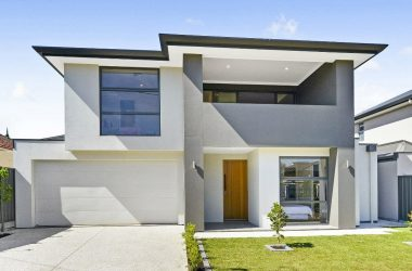 driveway view of double storey modern home with front garden and garage